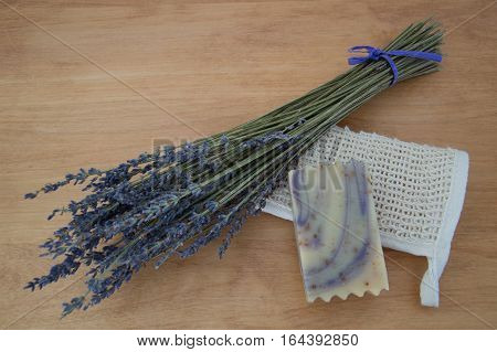 A bar of swirled lavender handmade goats milk soap on a light wooden table with a bouquet of dried lavender and a folded ramie washcloth. Natural light and shallow depth of field.