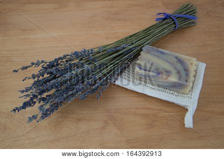 A single bar of swirled lavender goats milk soap resting on a folded ramie washcloth. A bouquet of dried lavender is next to the soap. All are placed on a light wood table. Natural light and shallow depth of field.