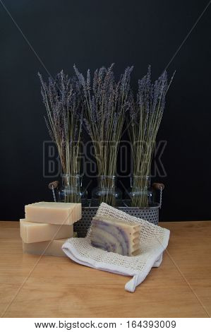 Three glass vases in a metal basket with sprigs of lavender against a black background with four bars of goats milk soap and a ramie washcloth in the foreground on a light wood table.