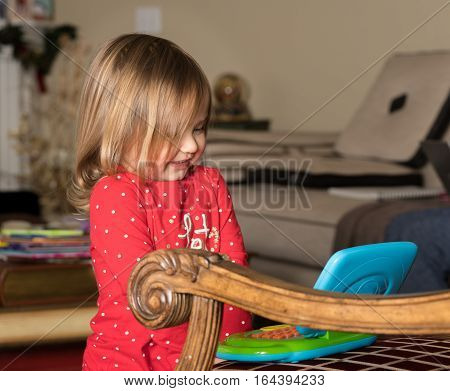 Young baby girl playing with a small plastic toy computer on a chair in her living room