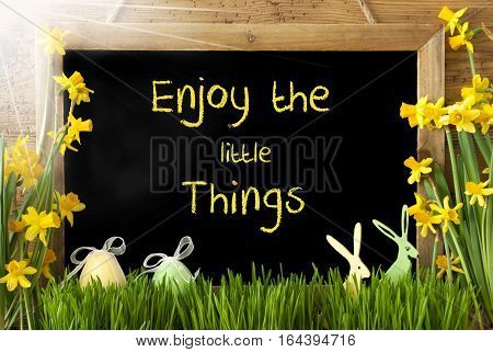 Blackboard With English Quote Enjoy The Little Things. Sunny Spring Flowers Nacissus Or Daffodil With Grass, Easter Egg And Bunny. Rustic Aged Wooden Background.