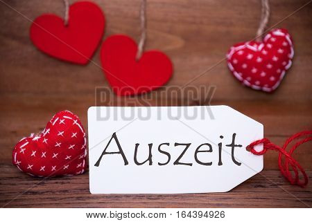 Label With German Text Auszeit Means Downtime. White Label With Red Textile Hearts. Retro Brown Wooden Background.