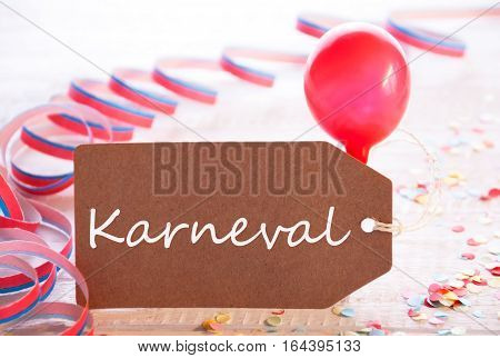 One Label With German Text Karneval Means Carnival. Party Decoration Like Streamer, Confetti And Balloon. Wooden Background With Vintage, Retro Or Rustic Syle