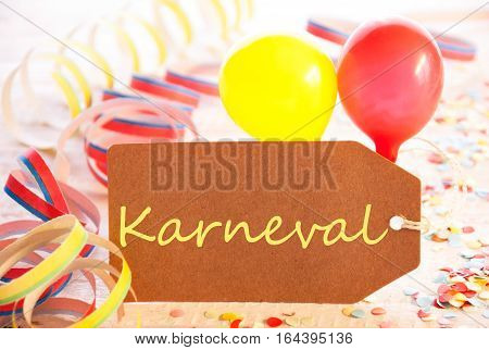 One Label With German Text Karneval Means Carnival. Party Decoration Like Streamer, Confetti And Balloons. Wooden Background With Vintage, Retro Or Rustic Syle