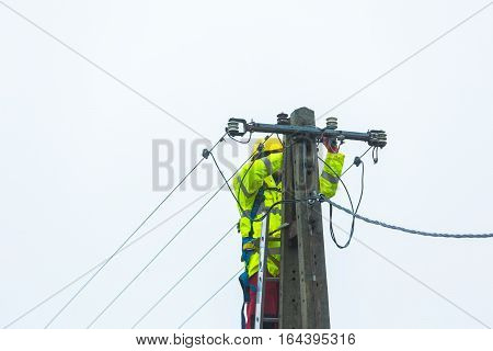 Electrician working on power lines. Failure of power lines on power pole.