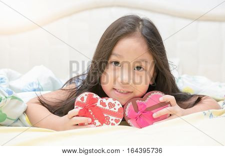 Girl Smile And Lie Down On Bed With Valentine Gift Box.