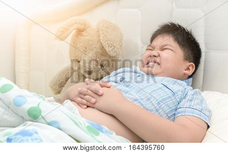 obese fat boy in him bed has a stomachache healthy concept