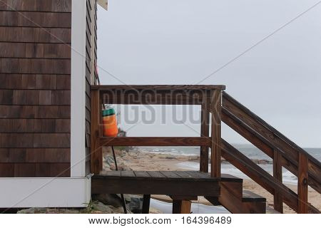 staircase to a beach side shed with orange buoy