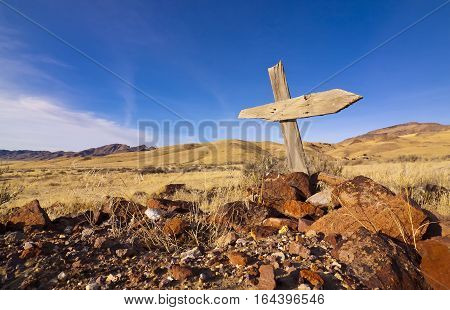 Old West grave with Ghost town and desert under blue sky.