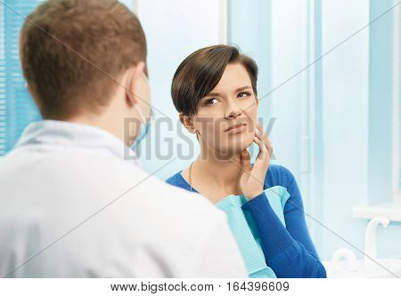 Young female patient visiting dentist office.Beautiful woman sitting at dental chair and complain of toothache.Dental clinic.Stomatology
