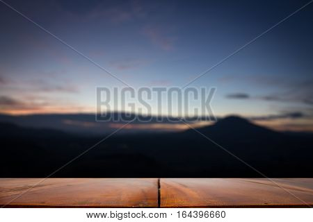 Empty top of wooden table or counter and sunnymountain blurred view of landscape background.For product display