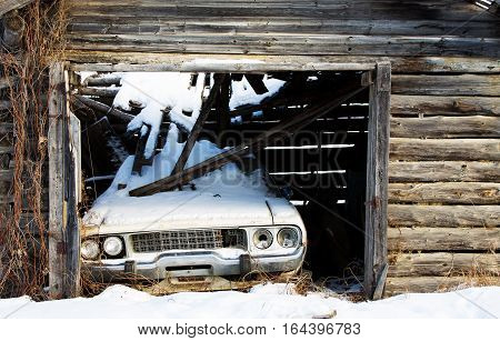 An abandoned vintage car backed into a log shed with a collapsed roof onto the car in winter