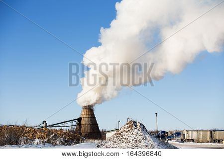 Heavy smoke drifting from a large wood burner at a sawmill yardsite