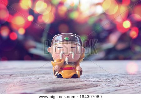 Small monk decoration on wooden table and abstract blur background