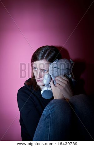 Young woman suffering from a severe depression/anxiety (color toned image; harsh lighting is used to convey the mood of unease)
