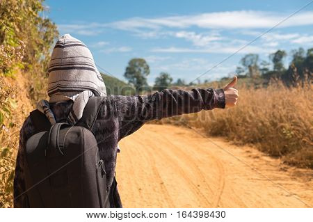Backpacker hitchhiking for a car in countryside road
