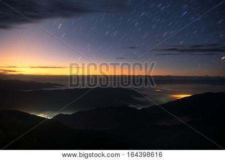 Star trails over twilight sky in morning with sea of cloud view from 1715 view point on  Doi Phukha in Nan province, Thailand.