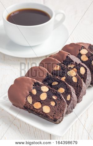 Homemade dark chocolate biscotti cookies with almonds covered with melted chocolate and cup of coffee vertical