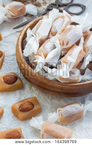 Homemade soft caramel candy with almonds vertical