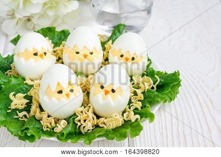 Little chicken in nest deviled eggs served with salad and dry ramen on white plate horizontal copy space