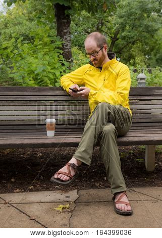 Man Sitting on Bench Looks up at Camera after looking at his phone