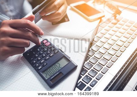 Close-up of female hands holding credit cards with calculator as online shopping or online payment concept.