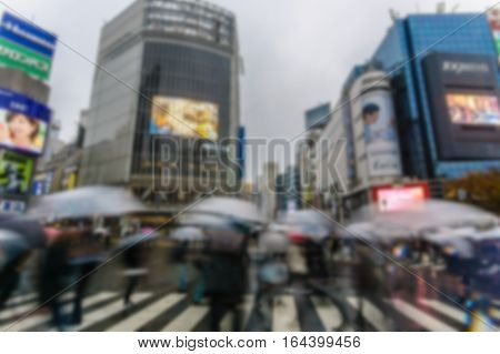 Blurred background.Pedestrians cross at Shibuya Crossing in n raining day in Tokyo Japan