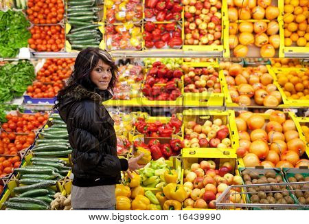 Beautiful young woman buying fruits and vegetables at a produce department of a supermarket/grocery store