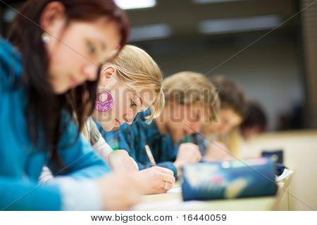 ziemlich weibliche College-Studentin, die eine Prüfung in einem Klassenzimmer voller Studenten (shallow DOF; Color zu sitzen