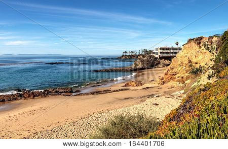 Blue sky over Diver's Cove Beach with the ocean at low tide in Laguna Beach, California, USA in winter