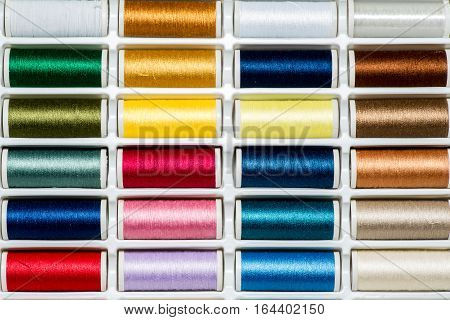 Collection of colored sewing threads on spool background