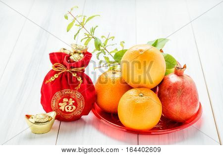 Chinese New Year,red Felt Fabric Bag With Gold Ingots And Oranges And Flower On White Wood Table Top
