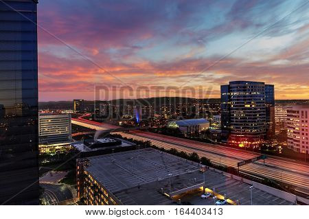 Sunrise over light trails and city lights on a highway in Irvine, California, USA.