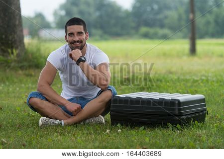 Man Sitting On Grass With Suitcase Of Drone