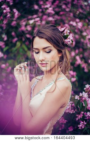 Portrait of young beautiful woman posing in spring blossom trees. Professional make-up and hairstyle. Perfect skin. Fashion photo.