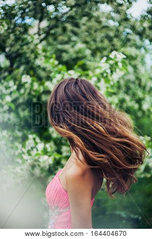 Young female with beautiful long hair in motion. Springtime. Floral background.