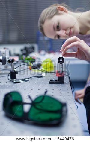 female scientist doing research in a quantum optics lab (color toned image)