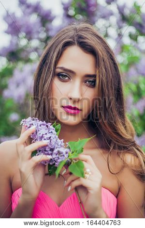 Portrait of young beautiful woman holding a lilac branch. Professional make-up and hairstyle. Perfect skin. Fashion photo.