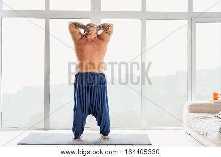 Sluggish male fatso is exercising in his apartment. He is raising hands behind his head. Focus on his nude back