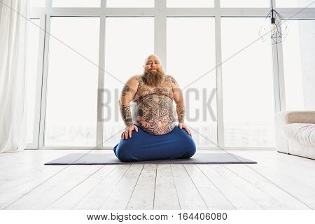 Joyful mature male fatso is resting after exercising. He is sitting on carpet in living room and smiling