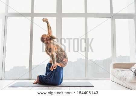 Calm man with overweight is meditating at home. He is kneeling and stretching arms up and down. His eyes are closed with relaxation