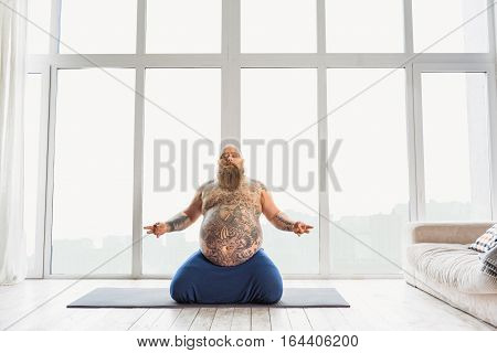 Serene fat man is doing meditation near window. He is sitting on mat. His bally is large with tattoo