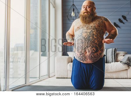I lost weight. Excited fat man is showing his body and looking at camera with shock. He is sitting on sport mat near window