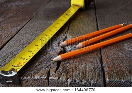 A close up image of a yellow carpenters tape measure and three wooden pencils.