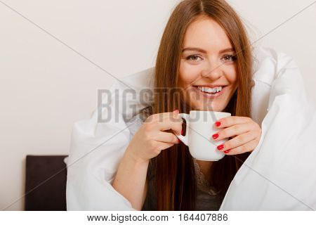 Smiling Woman Holding Cup Of Drink In Bed