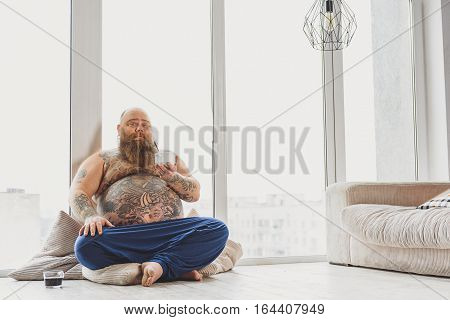 I need healthy food. Confident fat man is holding bowl of cereals. He is sitting on floor near cup of coffee