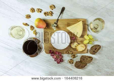 A photo of a tasting with glasses of red and white wine, different types of cheese, bread, nuts, pear, grapes, on a wooden board with copyspace