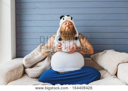 Carefree thick guy is eating zephyr with enjoyment. He is sitting on couch with closed eyes