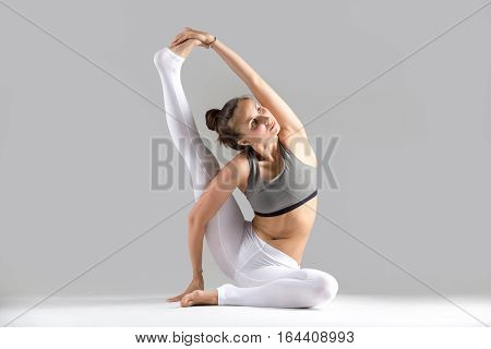 Young attractive woman practicing yoga, stretching in Compass exercise, Surya Yantrasana pose, working out wearing sportswear, white pants, indoor full length, isolated against grey studio background