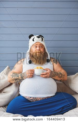 Mature thick guy is sitting on sofa and holding healthy cornflakes. He is looking at camera with confidence. Fatso is wearing funny panda hat